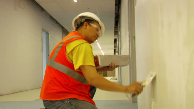 construction worker coats drywall on april 30 2012 in washington dc - stereotypically working class stock videos and b-roll footage