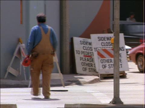 construction worker crossing street near construction site - solo uomini di età media video stock e b–roll