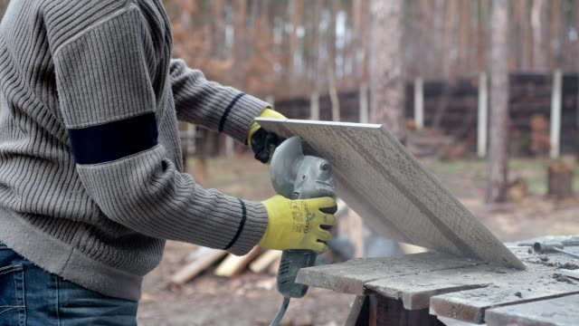 Construction worker cuts ceramic tiles.