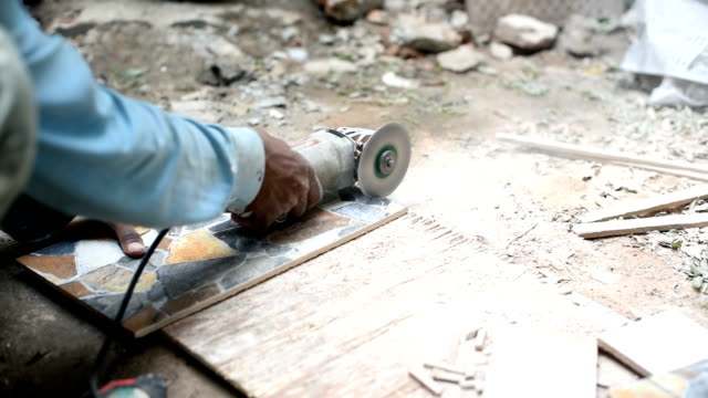 Construction worker cuts ceramic tiles with saw
