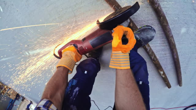 POV Construction worker cutting a metal pipe with an angle grinder