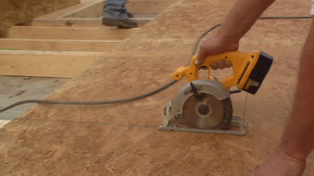 cu pan construction worker cutting board with miter saw / kalamazoo, michigan, usa - construction site stock videos and b-roll footage