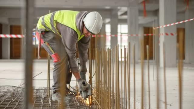 tu-bauarbeiter beim schneiden des stahlgitters auf dem boden eines im bau befindlichen industriegebäudes - arbeiter stock-videos und b-roll-filmmaterial