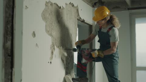 vídeos y material grabado en eventos de stock de trabajador de la construcción demoliendo la pared con taladro eléctrico - work tool