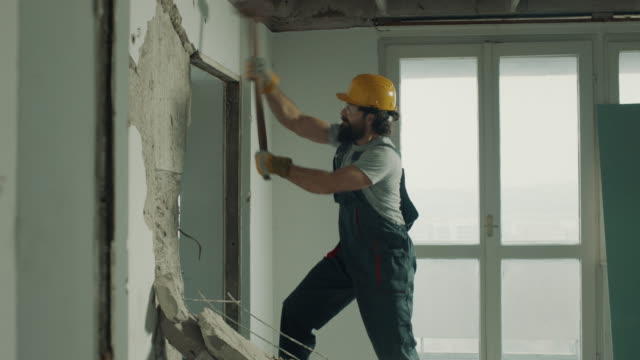 construction worker demolishing the wall with sledgehammer - wall building feature stock videos & royalty-free footage