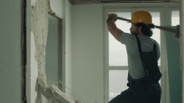 construction worker demolishing the wall with sledgehammer - sledgehammer stock videos & royalty-free footage