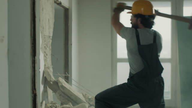 construction worker demolishing the wall with sledgehammer - demolishing stock videos & royalty-free footage