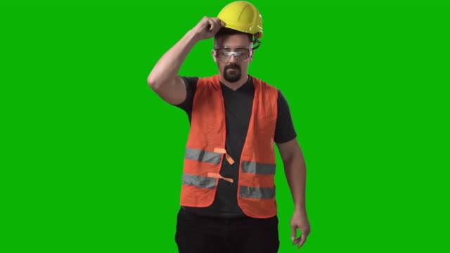 construction worker dressing looking at camera chroma green screen background - protective workwear stock videos & royalty-free footage