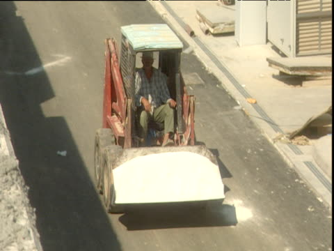 construction worker driving small red digger, full bucket of sand in scoop, around site for 2004 olympic games olympic village building site, athens - erektion stock-videos und b-roll-filmmaterial