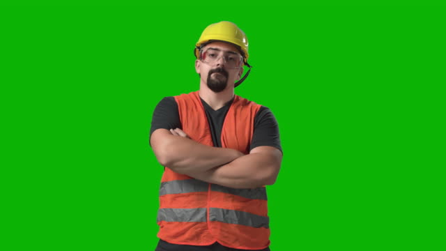 construction worker, engineer or architect standing looking at camera crossed hands chroma green screen background slow motion - arms crossed stock videos & royalty-free footage