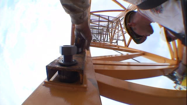 a construction worker fastens together a nut and bolt on a skyscraper crane. - bolt stock videos & royalty-free footage