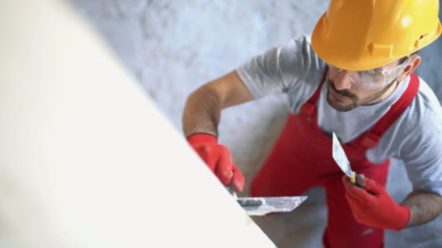construction worker finishing a wall. - installing stock videos & royalty-free footage