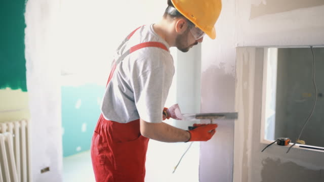 construction worker finishing a wall. - installare video stock e b–roll