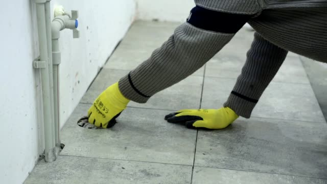 Construction worker fixes ceramic tile on the floor.