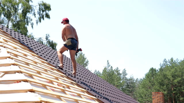 Construction worker fixes the metal roofing material with a screwdriver.