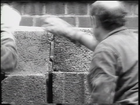 view construction worker grabs concrete block from pile / construction of berlin wall - 1961 stock-videos und b-roll-filmmaterial