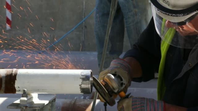 a construction worker grinds pipes near fuel storage tank at the vttv oil storage terminal a joint venture of vitol group and misc bhd in vasilikos... - fuel storage tank stock videos and b-roll footage