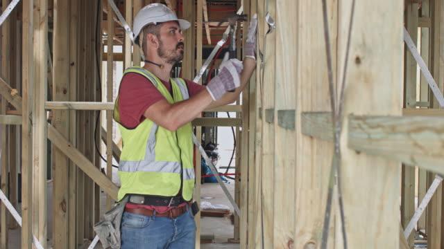 サイトで木の板を打って建設労働者 - 作業道具点の映像素材/bロール
