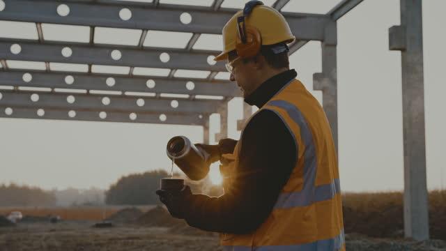vídeos y material grabado en eventos de stock de trabajador de slo mo construction tomando una taza de café en la obra por la mañana - refreshment
