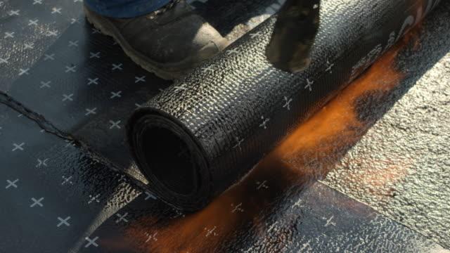 bauarbeiter heiz- und rollen bitumen rollen über eine oberfläche - asphalt stock-videos und b-roll-filmmaterial
