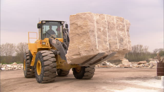 a construction worker helps direct a tractor preparing to unload a slab of limestone onto a platform. - limestone stock videos & royalty-free footage