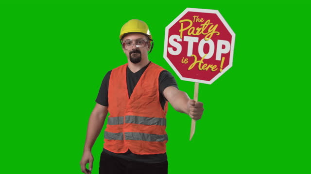 vídeos de stock e filmes b-roll de construction worker holding showing party stop sign chroma green screen background slow motion - máscara de proteção