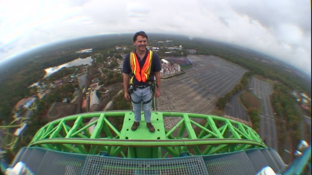 a construction worker in a safety harness stands on the top of a giant roller coaster. - safety harness stock videos & royalty-free footage