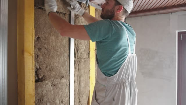 construction worker installing missing top pieces of mineral rock wool into the frame - insulator stock videos & royalty-free footage