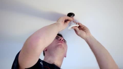 vídeos y material grabado en eventos de stock de trabajador de la construcción instala una lámpara en el techo. - luz led