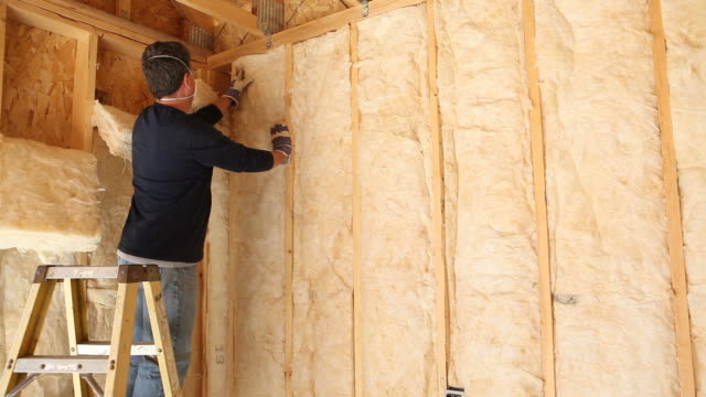 Construction Worker Insulating Wall with Fiberglass Batt