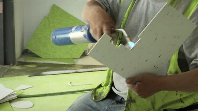 construction worker lays vinyl tile flooring on april 30 2012 in washington dc - sportschützer stock-videos und b-roll-filmmaterial