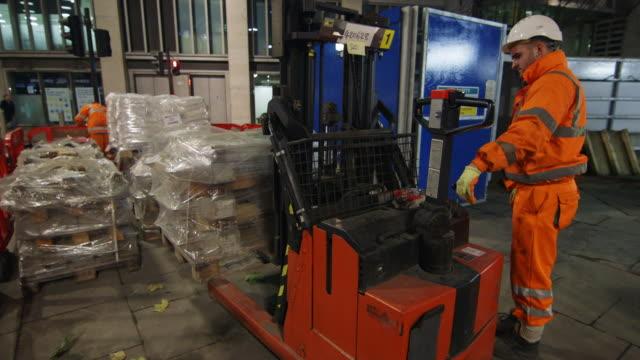 ws construction worker loading pallets on pallet jack at night / london, england, united kingdom - hubwagen stock-videos und b-roll-filmmaterial