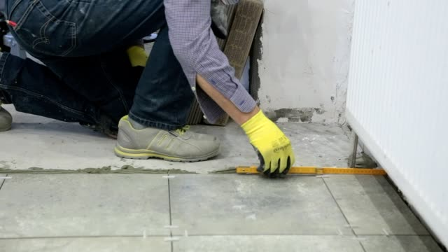 Construction worker makes measurements.