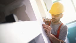 Construction worker marking cutting spots.