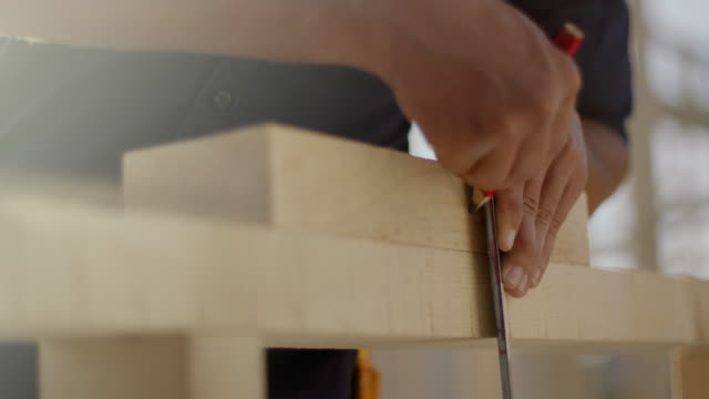 construction worker measuring wood for sawing - costruire video stock e b–roll