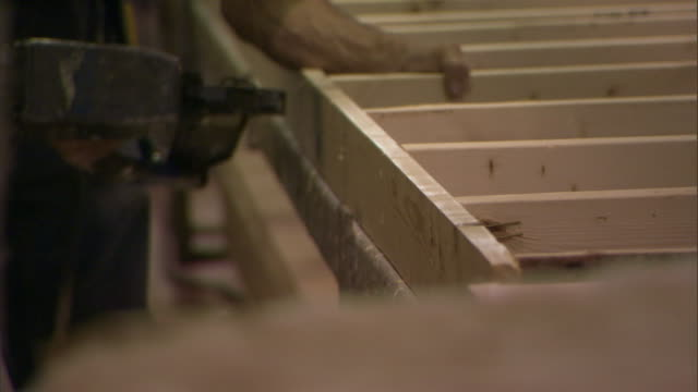 a construction worker nails together a wooden frame with a nail gun. - isoliermaterial stock-videos und b-roll-filmmaterial