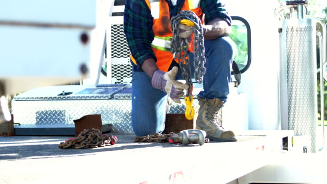Construction worker on crane picking up hook and chain