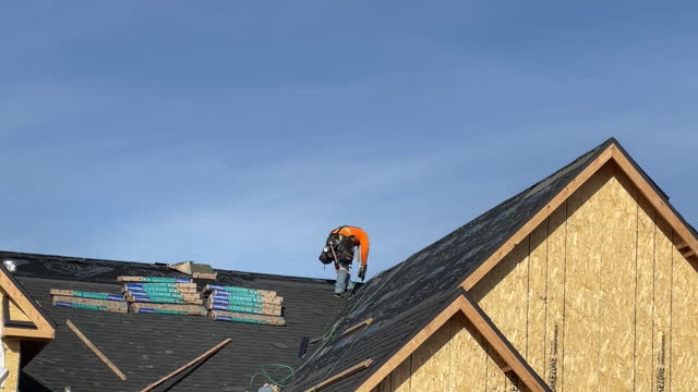 vídeos de stock, filmes e b-roll de construction worker on rooftop of newly built residential building in lehi, utah, u.s., on wednesday, december 16, 2020. - lehi