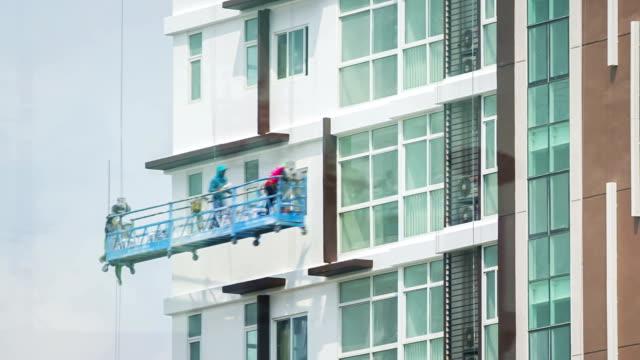 stockvideo's en b-roll-footage met construction worker on scaffolding painting the building - schilderen