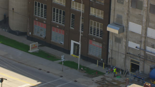 ws aerial pov construction worker outside the entrance of congra flour mill / alton, illinois, united states - flour mill stock videos & royalty-free footage