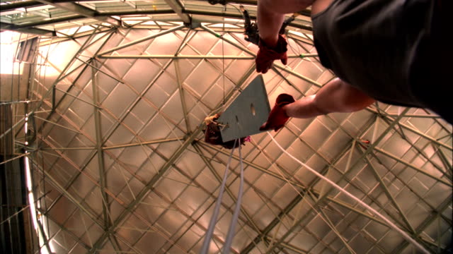 vídeos de stock, filmes e b-roll de a construction worker passes a steel beam to his co-worker as he hangs from a harness inside a modern skyscraper. available in hd. - arnês de segurança