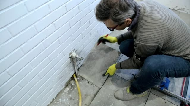 Construction worker plans to install ceramic tiles on the floor.