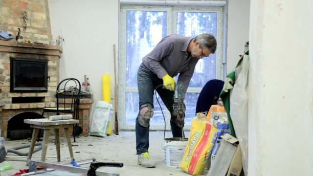 construction worker prepares building glue. - ukrainian ethnicity stock videos and b-roll footage