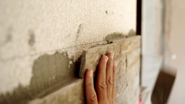 construction worker puts a stone on the wall - realizzazione video stock e b–roll