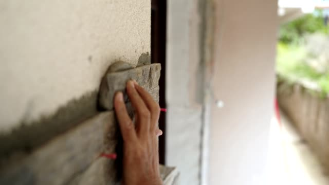 construction worker puts a stone on the wall - professional painter stock videos and b-roll footage