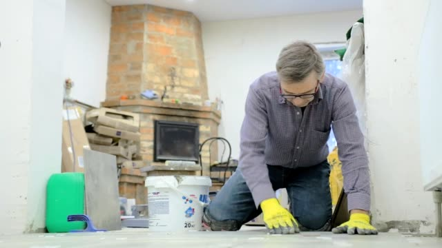 Construction worker puts and fixes ceramic tiles on the floor.