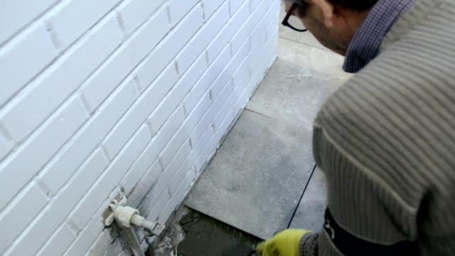 Construction worker puts ceramic tiles on the floor.