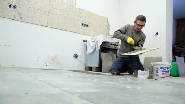 建設労働者は、床にセラミック タイルを置きます。 - 東ヨーロッパ民族点の映像素材/bロール