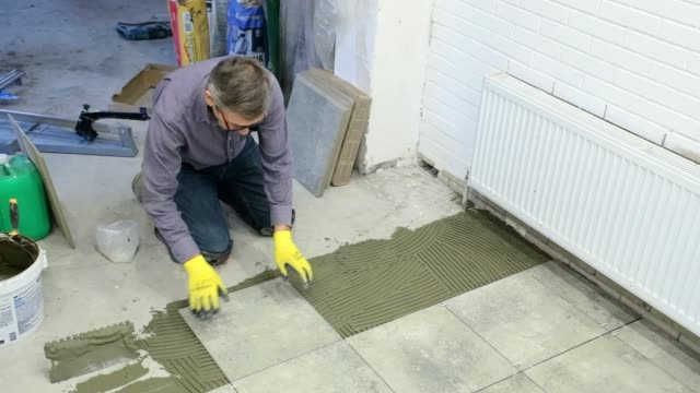 construction worker puts ceramic tiles on the floor. - ukrainian ethnicity stock videos and b-roll footage