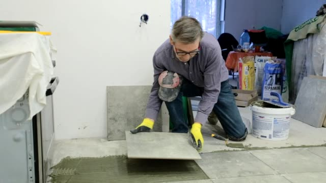 construction worker puts ceramic tiles on the floor. - washing up glove stock videos & royalty-free footage